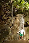 dad cooling off in a waterfall on Families in Nature trip to Costa Rica