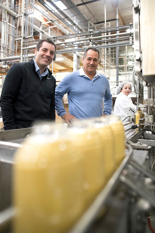 Domonic Biggi, CEO of Beaver Foods, and his nephew Jeffrey, watch as a machine fills bottles of sweet mustard at the company's Hillsboro manufacturing plant.<br /> Photo by Jaime Valdez