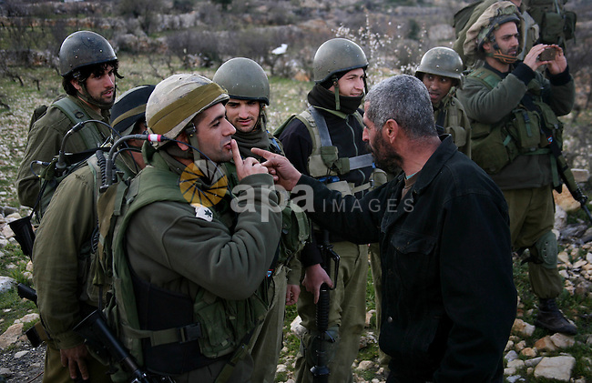 Israeli soldiers face Palestinians protesters who gathered for a protest against a Jewish settlement near the West Bank village of Beit Omar, close to the city of Hebron and the settlement of Karmei Tzur, on 25 February 2012. Photo by Mamoun Wazwaz