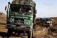 Trucks try to overcome the mud infested track that they must pass in order to reach Tarin Kot