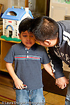 Education preschool 3-4 year olds start of day separation sad boy saying goodbye to his father vertical.holding security object a small car