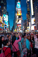 Tourists from Asia taking pictures on Times Square in New York City, USA