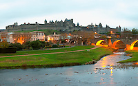 Carcassonne. Languedoc. View over the old city. The old bridge across the Aude river. Illuminated in early morning. A rainy and misty winter day. France. Europe.