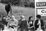 Middle aged couples sit on a wall of the car park in front of a cafe. They have stopped for a cup of tea. Derbyshire Peak district. England 1970