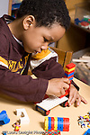 Education Preschool 3-4 year olds boy playing with colored plastic Lego bricks vertical