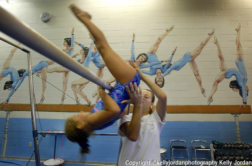 As a product of the Garguilo Gymnastic Center in Daytona Beach, Amanda Shaw, right, now coaches at the center as she assists Danielle Lipton, 9, of Ormond Beach on the uneven bars Wednesday afternoon, July 31, 2002 at the Garguilo Gymnastic Center in Daytona Beach. The center is in jeopardy of losing funding due to city budget cuts.(kelly Jordan)..