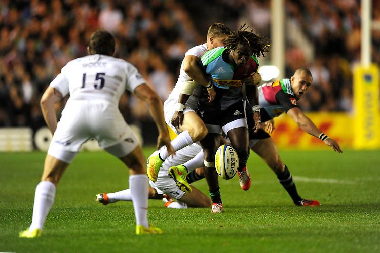 Marland Yarde of Harlequins loses the ball as he is tackled during the Premiership Rugby Round 2 match between Harlequins and Saracens at The Twickenham Stoop on Friday 12th September 2014 (Photo by Rob Munro)