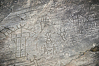 Prehistoric Petroglyph, rock carving, of houses on wooden ploes with men fighting carved by the Camunni people in the ,iddle to late iron age between  900-1200 BC, Rock no 18, Seradina II area , Seradina-Bedolina Archaeological Park, Valle Comenica, Lombardy, Italy