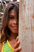 Mato Grosso State, Brazil; young caboclo girl wearing a green and yellow top partly hidden behind a tree trunk.