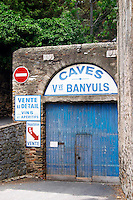 Caves Veuve Banyuls, wine cellar sign in blue. Advertising sale of wine in the wine shop. Collioure. Roussillon. A door. The wine shop and tasting room. France. Europe.