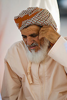 Oman, Buraimi, Omani man, seated, with traditional massar headcloth
