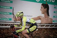 an elite women's racer (Rozanne Slik?) with blooded eye passing in front of the contrasting title sponsor's billboard<br /> <br /> Superprestige Gavere 2014