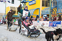 Jodi Bailey and team leave the ceremonial start line with an Iditarider at 4th Avenue and D street in downtown Anchorage, Alaska during the 2015 Iditarod race. Photo by Jim Kohl/IditarodPhotos.com