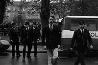 """""""Portai [Portay], Picard, Me Cathala, Me Bouscatel, Me Rastoul"""". Place Wilson. 30 novembre 1976. Vue d'ensemble de face de Christian Portay (accusé) arrivant sur le lieu de la reconstitution ; au 2nd plan policiers, fourgon de police ; en arrière-plan square, des personnes regardent la scène, enseigne du """"Gaumont"""". Cliché pris le jour d'une reconstitution judiciaire dans le cadre de l'affaire du meurtre de René Trouvé. Observation: Affaire René Trouvé-Birague : le 19 février 1976, le journaliste René Trouvé est assassiné d'une balle dans la tête, par deux inconnus, alors qu'il regagne son domicile au 33 rue Bayard."""
