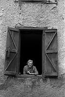 Village d'Arguenos (Haute-Garonne). 10 janvier 1978. Plan rapproché d'une vieille dame à la fenêtre de sa maison (vue de face).