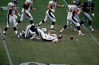OAKLAND, CA - Quarterback John Elway of the Denver Broncos fumbles the football during a game against the Oakland Raiders at the Oakland Coliseum in Oakland, California on October 19, 1997. (Photo by Brad Mangin)