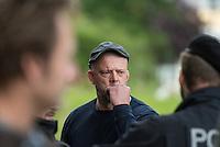 """Am Freitag den 10. Juli 2015 wurde die erste von zwei Containerunterkuenften fuer Fluechtlinge aus dem Buergerkrieg in Syrien im Berliner Bezirk Marzahn-Hellersdorf bei einem """"Tag der offenen Tuer"""" fuer die Anwohner geoffnet. Dies geschah, um die im Stadtteil weit verbreitete Angst und die Vorurteile abzubauen. Der Andrang der Anwohner war sehr gross.<br /> Gegen die Errichtung der zwei Containerunterkuenfte protestierten eine handvoll Nazis und Hooligans. Zum Teil wurden rassistische Parolen gebruellt.<br /> Zum Schutz der Containerunterkuenfte vor rassistischen Protesten waren Mitarbeiter einer Securityfirma und zwei Hunderschaften der Polizei vor Ort.<br /> Im Bild: Der Hellersdorfer Nazi und Wortfuehrer gegen die Wohncontainer Rene Uttke. Er bekam im Laufe des Nachmittags mehrfach einen Platzverweis von der Polizei, der jedoch nicht umgesetzt wurde. So konnte er unter den Augen von Polizeibeamten ungehindert Fluechtlingsunterstuetzer provoziereb und filmen. Am Morgen hatten Polizeibeamte seine Wohnung durchsucht, nachdem bei Fluechtlingsunterstuetzern in der Nacht scharfe Munition als Drohung gelegt wurde. Bei der Hausdurchsuchung wurde scharfe Munition sowie eine Waffenbesitzkarte (Waffenschein) gefunden. Uttke hatte in der Vergangenheit politische Gegner mit symbolischen Pistolenschuessen bedroht.<br /> 10.7.2015, Berlin<br /> Copyright: Christian-Ditsch.de<br /> [Inhaltsveraendernde Manipulation des Fotos nur nach ausdruecklicher Genehmigung des Fotografen. Vereinbarungen ueber Abtretung von Persoenlichkeitsrechten/Model Release der abgebildeten Person/Personen liegen nicht vor. NO MODEL RELEASE! Nur fuer Redaktionelle Zwecke. Don't publish without copyright Christian-Ditsch.de, Veroeffentlichung nur mit Fotografennennung, sowie gegen Honorar, MwSt. und Beleg. Konto: I N G - D i B a, IBAN DE58500105175400192269, BIC INGDDEFFXXX, Kontakt: post@christian-ditsch.de<br /> Bei der Bearbeitung der Dateiinformationen darf die Urheberkennzeichnung in den EXIF- und  I"""