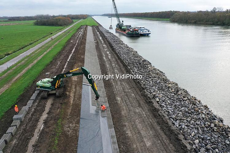Foto: VidiPhoto<br /> <br /> ZOELEN – Personeel van aannemerscombinatie PARK (Van den Herik/BAM), legt dinsdag 10.000 grasbetontegels en 6600 ton stortstenen aan de oostzijde van de dijk langs het Amsterdam-Rijnkanaal, ter hoogte van Zoelen in de Betuwe. Dijkverbetering in het hoogwaterseizoen is ongebruikelijk, maar in dit geval noodzakelijk. Tijdens de laatste inspectie bleek namelijk dat zo'n 450 meter van de dijk ter plaatse was verzakt. Omdat daar ook sprake is van een muizenplaag en muizen tal van gaten in de dijk hebben gegraven, is onder de klinkers speciaal muizengaas aangebracht. Aan de binnenzijde van de dijk wordt gedraineerd tegen kwelwater. De werkzaamheden worden uitgevoerd in opdracht van Rijkswaterstaat en moeten voor 1 december gereed zijn.