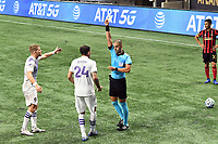 ATLANTA, GA - AUGUST 29: Referee Nima Saghafi issues a yellow card caution to Kyle Smith #24 of Orlando City during a game between Orlando City SC and Atlanta United FC at Marecedes-Benz Stadium on August 29, 2020 in Atlanta, Georgia.