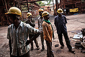 Essar Steel employees take a break after the end of their shift outside the plant in Kirandul, Chattisgarh, India. The plant that has been closed for over a year because of Maoist attack on their iron ore slurry pipeline and the plant.  Photograph: Sanjit Das/Panos