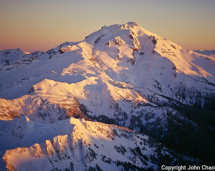 Aerial of sunset highlighting snowy ridges at Glacier Peak, Glacier Peak Wilderness Area, North Cascades Mountain Range, Washington State