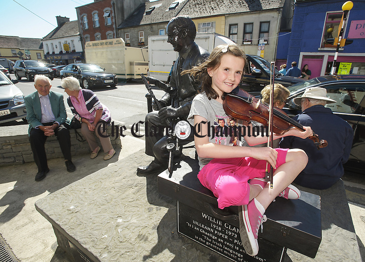 Cavan's Grainne Brady playing tunes  at the Willie Clancy monument at main Street Miltown Malbay during the Willie Clancy Festival. Photograph by John Kelly.