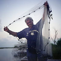 Edison Dardar arranges his cast net as he fishes for shrimp off the dock near his house on Isle Jean Charles, Louisiana. Although commercial fishing was banned after the oil spill, many local residents continued to catch fish, shrimp and crabs for their own consumption. Edison is a retired oysterman. The shrimp he catches less than a mile from his house are a staple of the meals he and his wife prepare. For many Native American people on the coast, self-harvested seafood is a mainstay that allows for continued self-sufficiency.
