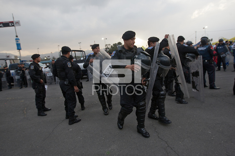 Mexican police officers in riot gear form a perimeter around a bus of USA fans arriving for the USA vs. Mexico World Cup Qualifier at Azteca stadium in Mexico City, Mexico on March 26, 2013.