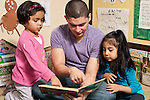 Education preschool 3-4 year olds young male teacher reading to two girls