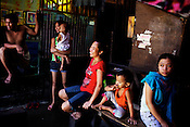 A family shares a light moment in their Shanty-town, Sitio Aroma in Barangay 105, Manila in Philippines. Photo: Sanjit Das
