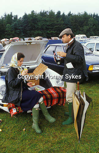 Windsor, Berkshire. 1985<br /> At Windsor Great Park polo ground a fashionable Sloane Ranger couple enjoying an alfresco picnic from their convertible Porsche 911 SC Cabriolet. She's on a Bucks Fizz, but made with Henkell Trocken, a German sparkling white wine, while he is taking it neat. They are both dressed as fashion dictates for the occasion in new un-muddied green Hunter Wellington Boots and his and her blue Burberry waxed jackets, absolutely in vogue at the time<br /> She has donned a Hermes headscarf, while he is in a tweed flat cap.  She's on a Bucks Fizz, but made with Henkell Trocken, a German sparkling white wine, while he is taking it neat.