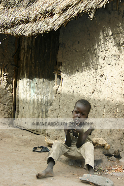 """A boy sits in front of a hut (""""tukul"""") in the Rumbek market, South Sudan."""