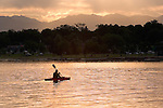 Man kayaking at Sloans Lake with the Rocky Mountains behind, Denver, Colorado.