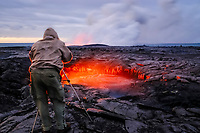 Hiker taking photos at sunrise, Skylight and flowing lava, Waikupanaha ocean entry lava flow area, East of Hawaii, USA Volcanoes National Park, Kalapana, Hawaii, USA, The Big Island of Hawaii, USA