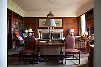 The wood panelled ibrary, furnished with antique chairs and floor-to-ceiling bookcases
