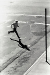 Man running across city street.