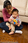 language development 16 month old toddler boy talked to by mother shown how propeller on toy airplane works Asian American Chinese vertical EVOstock