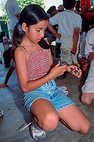 girl examines Kemp's ridley sea turtle hatchlings, Lepidochelys kempii, during educational program at turtle research camp, Rancho Nuevo, Mexico, Gulf of Mexico, Caribbean Sea, Atlantic Ocean