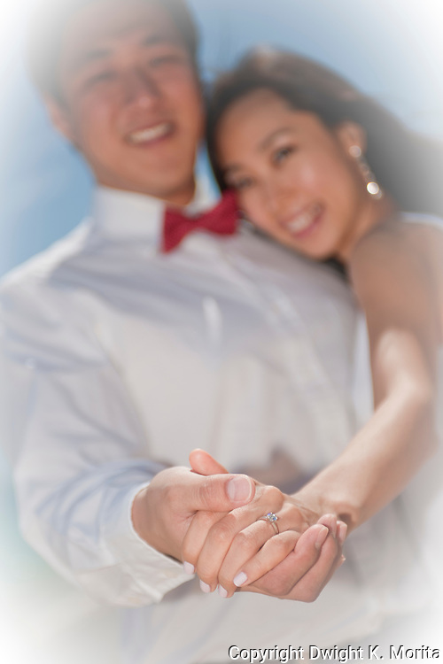 Asian bride and groom dance on Lanikai beach, showing the wedding ring as the couple looks forward to their life as a married couple following their wedding.