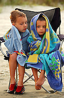 Two young boys stay warm in their towels at the ocean beach.
