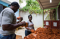 Haiti, Port-au-Prince. Artisan business, Papillon. Produce ceramics, jewelry, t-shirts. Over 300 women on payroll (men work her as well), making about $15 a day. Unloading the kiln with ceramic mugs.