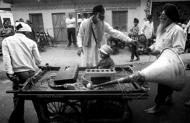 11.2010 Bundi (Rajasthan)<br /> <br /> Man carrying music and a baby during guru Nanak festival.<br /> <br /> Homme transportant un enfant et la musique pendant la fête de guru Nanak.
