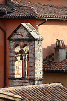 Todi:  A small nice bell-tower that is surrounded by the characteristic roofs covered by reddish shingles. The view gives back the warm atmosphere of the historical center of the old town.