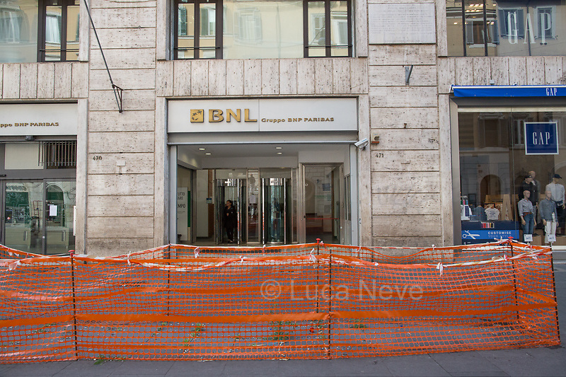 """Bank: open.<br /> <br /> Via del Corso.<br /> <br /> Rome, 12/03/2020. Documenting Rome under the Italian Government lockdown for the Outbreak of the Coronavirus (SARS-CoV-2 - COVID-19) in Italy. On the evening of the 11 March 2020, the Italian Prime Minister, Giuseppe Conte, signed the March 11th Decree Law """"Step 4 Consolidation of 1 single Protection Zone for the entire national territory"""" (1.). The further urgent measures were taken """"in order to counter and contain the spread of the COVID-19 virus"""" on the same day when the WHO (World Health Organization, OMS in Italian) declared the coronavirus COVID-19 as a pandemic (2.).<br /> ISTAT (Italian Institute of Statistics) estimates that in Italy there are 50,724 homeless people. In Rome, around 20,000 people in fragile condition have asked for support. Moreover, there are 40,000 people who live in a state of housing emergency in Rome's municipality.<br /> March 11th Decree Law (1.): «[…] Retail commercial activities are suspended, with the exception of the food and basic necessities activities […] Newsagents, tobacconists, pharmacies and parapharmacies remain open. In any case, the interpersonal safety distance of one meter must be guaranteed. The activities of catering services (including bars, pubs, restaurants, ice cream shops, patisseries) are suspended […] Banking, financial and insurance services as well as the agricultural, livestock and agri-food processing sector, including the supply chains that supply goods and services, are guaranteed, […] The President of the Region can arrange the programming of the service provided by local public transport companies […]».<br /> Updates: on the 12.03.20 (6:00PM) in Italy there 14.955 positive cases; 1,439 patients have recovered; 1,266 died.<br /> <br /> Footnotes & Links:<br /> Info about COVID-19 in Italy: http://bit.do/fzRVu (ITA) - http://bit.do/fzRV5 (ENG)<br /> 1. March 11th Decree Law http://bit.do/fzREX (ITA) - http://bit.do/fzRFz (ENG)<br /> 2. http://bit.do/f"""