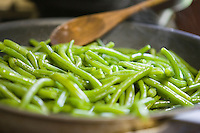 Fresh greenbeans being cooked in a skillet.
