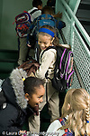 Education Elementary school Grade 2 group of girls going up stairs wearing winter coats and backpacks arrival vertical