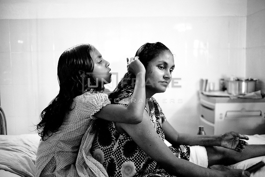 Younger daughter of garments worker Roksana, helps her mother to dress her hair at Anam medical college hospital. Roksana is severally injured in the building collapse. Savar, near Dhaka, Bangladesh