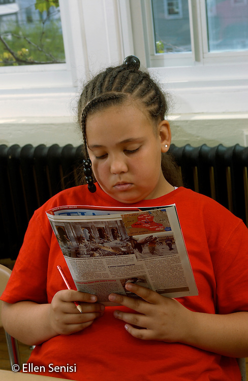 MR / Schenectady, NY / .Yates Arts in Education Magnet School / urban public elementary school / Grade 5.Girl (10, African-American and Caucasian) reads current events magazine written for fifth grade students. (Current events is component of 5th grade social studies curriculum)..MR: AD-g5a She16..© Ellen B. Senisi