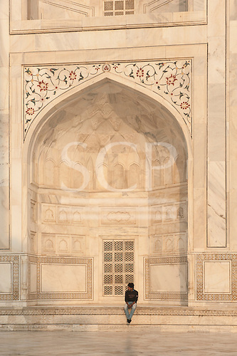 Agra, Uttar Pradesh, India. A man sitting in the alcove of the Taj mahal.