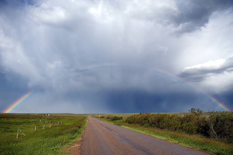 Rainbow spanning a prairie road following a summer thunderstorm